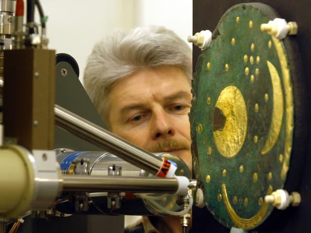 Ein Mann beobachtet eine Maschine, die auf die Himmelsscheibe von Nebra gerichtet ist