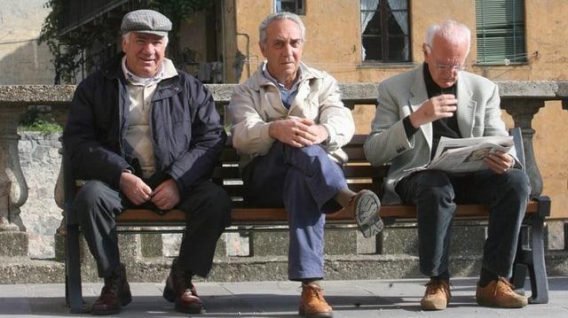 Drei ältere Männer auf Bank sitzend