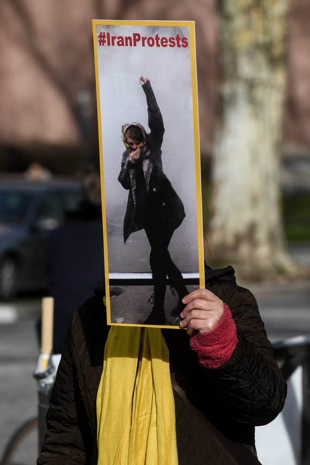 """Frau hält Plakat mit der Aufschrift """"IranProtests"""" hoch."""