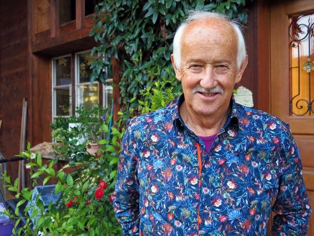 Porträt von Mann in geblümten Hemd vor Holzhaus mit grünen Pflanzen.