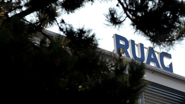 Das Firmenlogo von Ruag auf einen Gebäudedacht, im Vordergrund ein Nadelbaum.