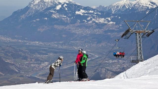 Skifahrer auf der Piste, dahinter das grüne Rheintal in der Ferne.