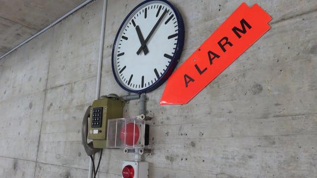 Eine Uhr an der Wand, darunter ein Telefon und ein roter Knopf, auf den ein grosses Schild weist. Auf diesem steht: Alarm.
