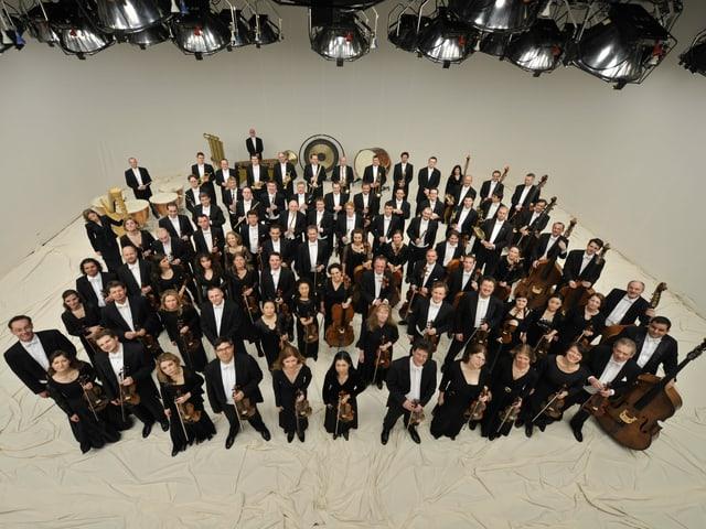 Viele Menschen - Musikerinnen und Musiker des Orchesters - stehen mit Instrumenten und Anzügen und Kleidern da und schauen in die Kamera.