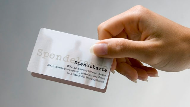 Eine Frauenhand hält eine Spendekarte von Swisstransplant.