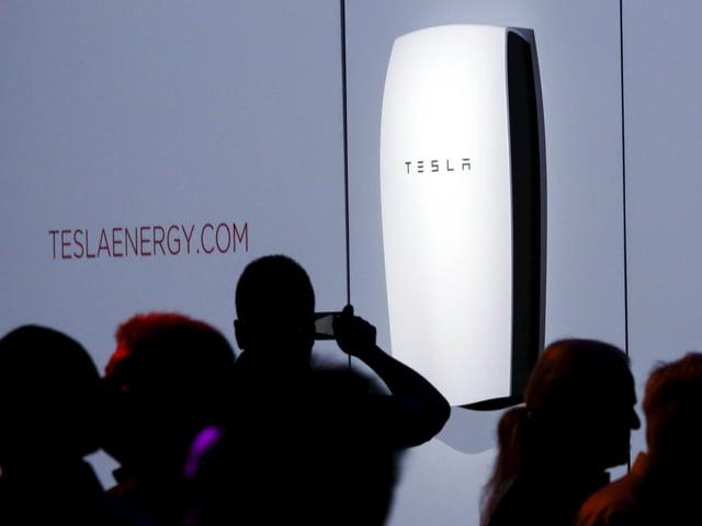 Silhouetten von Menschen vor einer Grossbatterie, die von der Firma Tesla entwickelt wurde.