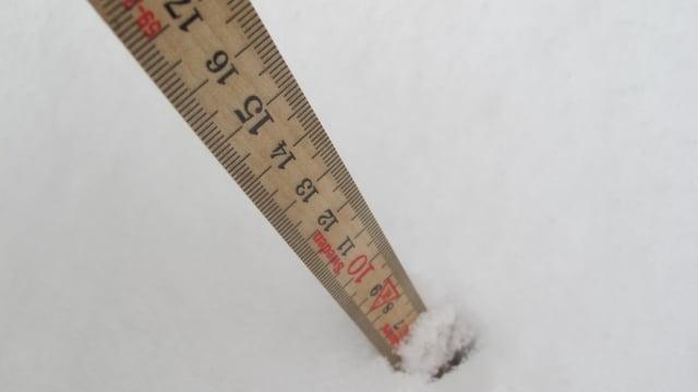 Ein Klappmeter steckt im Schnee.
