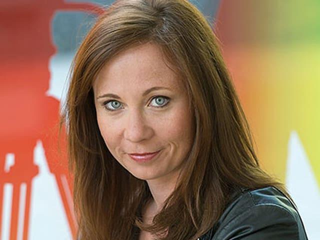 Porträt einer jungen Frau mit dunklen langen Haaren und hellblauen Augen.