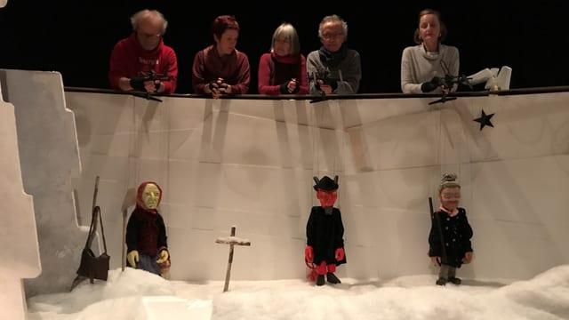 Bühne mit grossen Marionettenfiguren und im Hintergrund die Spieler, die die Puppen halten.