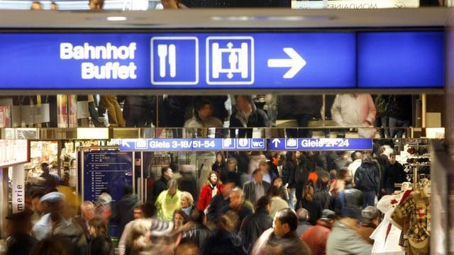 """Gewusel im Zürcher Hauptbahnhof, oben leuchtet ein Schild """"Bahnhof Buffet""""."""