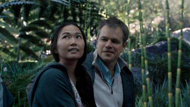 Ein Mann und eine Frau, zu sehen sind sie ab der Schulter. Die Frau schaut in die Höhe, der Mann schaut die Frau an. Um sie herum eine grüne Wiese. Da die beiden Menschen so klein sind, sind die Grashalme so dick wie junge Baumstämme.