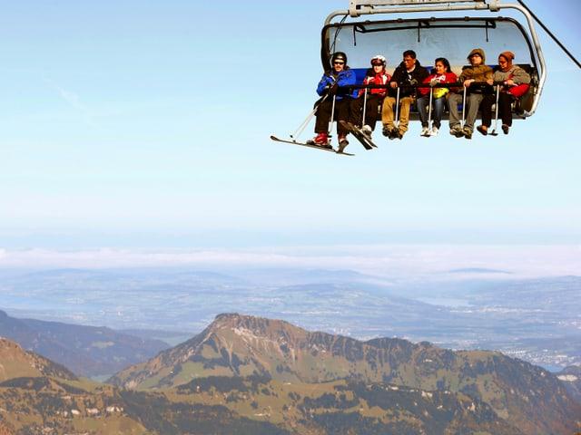 Sechs Leute sitzen in einer offenen Gondel. Im Hintergrund eine Berglandschaft.