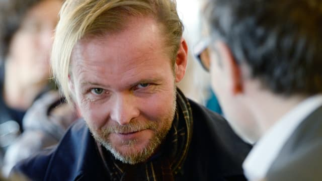 Auf dem Bild sieht man ein Porträt des Schweizer Autoren Christian Kracht, wie er verschmitzt in die Kamera lächelt.