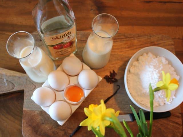 Zutaten für Eierlikör auf einem Brett.