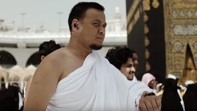 Ein Mann vor der Kaaba in Mekka hat einen Knopf im Ohr.