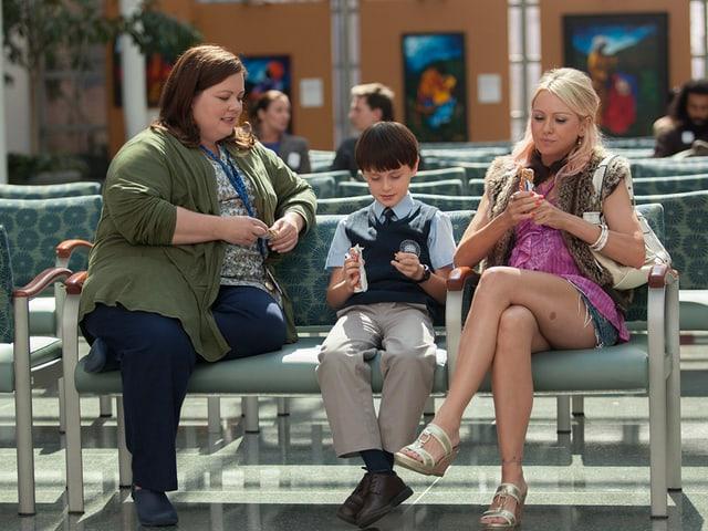 Zwei Frauen und ein Junge sitzen auf der Bank.