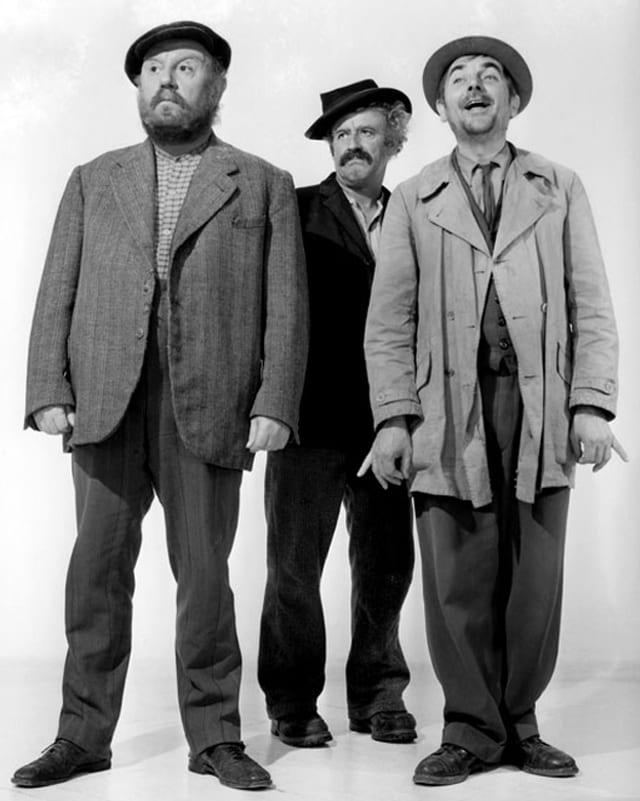 Drei Männer stehen zusammen.