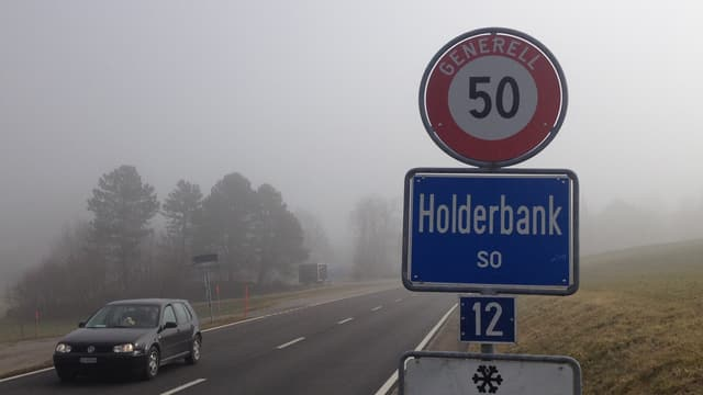 Ortsschild von Holderbank, nebliges Wetter, ein Auto fährt vorbei, im Hintergrund sind Bäume knapp durch den Nebel zu sehen.