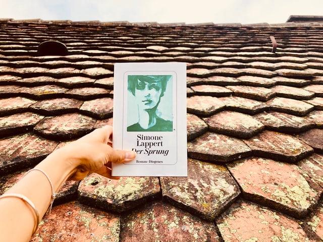 Annette König hält den Roman «Der Sprung» von Simone Lappert vor ein Ziegeldach