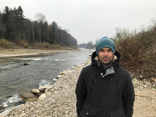 Mann mit Mütze an Fluss.