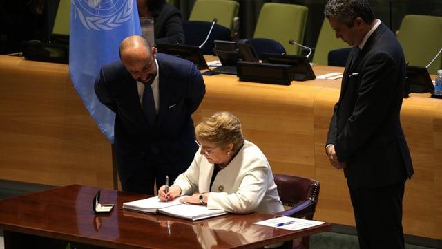 Sie sitzt im weissen Jackett an einem Tisch. Neben ihr stehen zwei Männer, dahinter die UNO-Flagge.