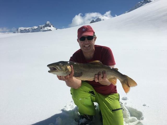 Daniel Kilian hält einen grossen Namaycush in den Händen. Er ist auf dem Melchsee, der gefroren und schneebedeckt ist.