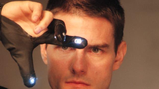 Mann betrachtet seine beiden Finger, die mit kleinen Lampen versehen sind