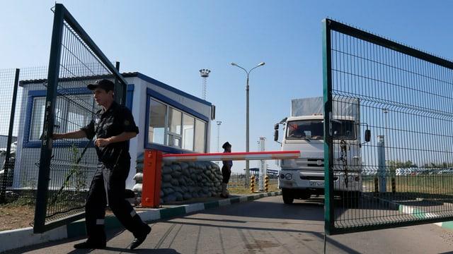 Ein Zöllner stösst ein Grenztor auf. Hinter der Barriere steht ein weisser Lastwagen.