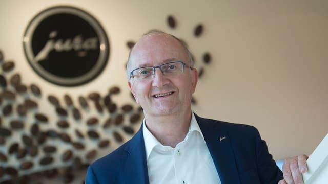 Mann mit Brille, im Hintergrund Kaffeebohnen an einer Wand