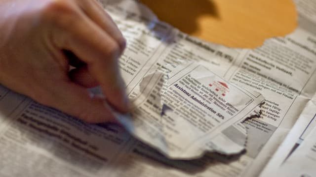 Eine Hand hält eine aus einer Zeitung ausgerissene Stellenanzeige.