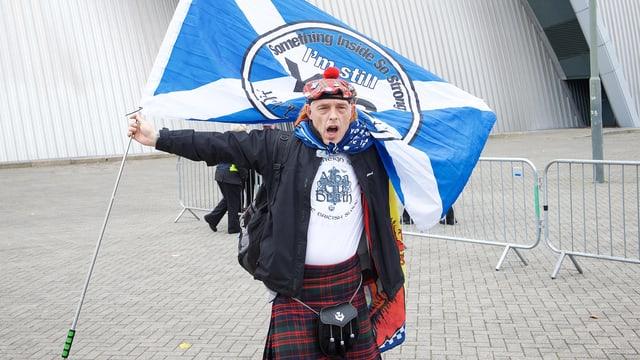 Mann in Schottenrock mit schottischer Fahne vor einem Kongressgebäude.