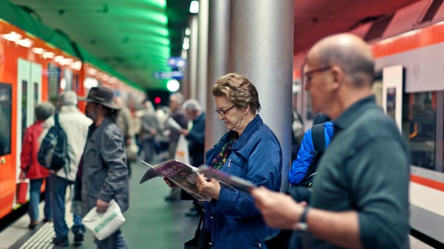 Bahnpassagiere stehen auf dem Perron im Bahnhof und lesen Zeitungen.