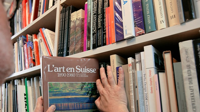 Eine Hand nimmt ein Buch aus einem Bücherregal.