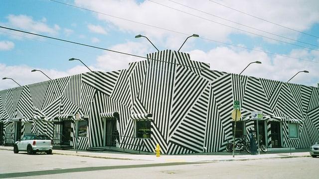 Ein Haus ist über und über mit schwarz-weissen Streifen bemalt.