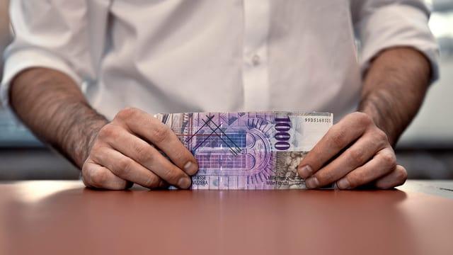 Zwei Hände halten ein Geldbündel mit 1000er Noten.