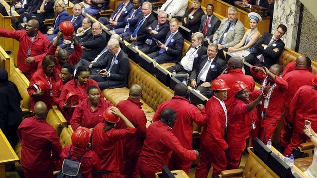 In Rot gekleidete Mitglieder der Opposition verlassen das Parlament.