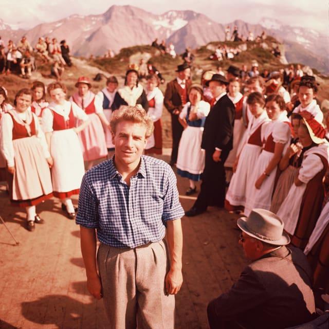 Hannes Schmidhauser steht in der Mitte gekleidet in ein kariertes Hemd. Um ihn herum stehen mehrere Frauen in Trachten. Im Hintergrund die Berge.