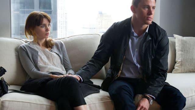 Eine Frau und ein Mann sitzen auf einem beigen Sofa.
