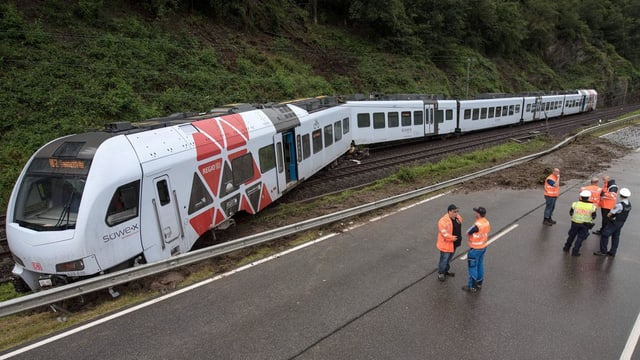 Ina vista totala dal tren cun la locomotiva ch'è siglida or dal binari.