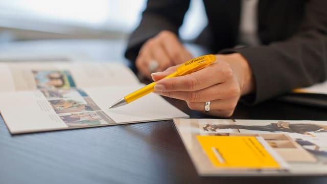 Eine Frau hält einen Postfinance-Kugelschreiber und zeigt etwas in einer Broschüre.