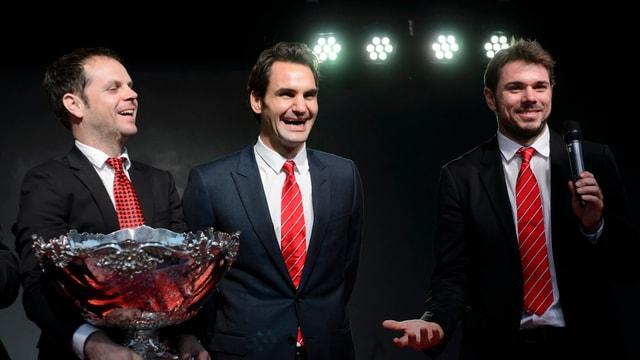 Severin Lüthi hält die Davis-Cup-Schüssel, daneben stehen breit lachend Roger Federer und Stan Wawrinka.