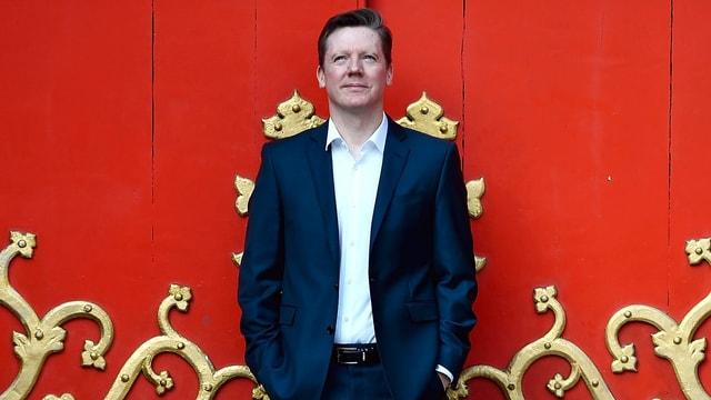 Fergus Linehan steht vor einer roten Wand.