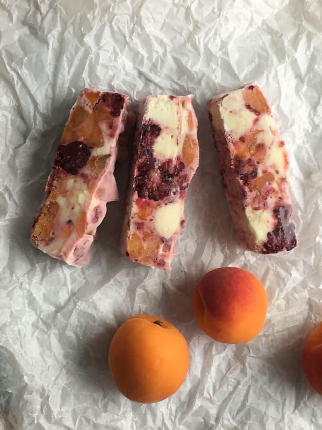 Glace mit Brombeeren und daneben zwei Aprikosen.