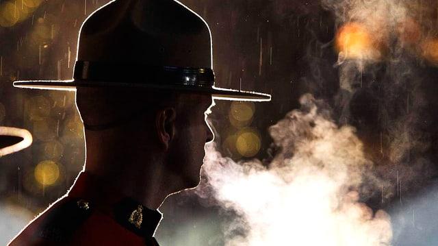 Kanadischer Mounty-Polizist im Gegenlicht fotografiert. Aus seiner Nase strömt eine Atemdampfwolke.
