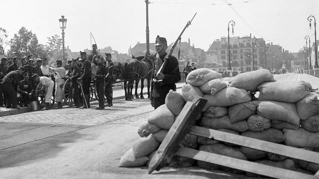 Eine Barrikade aus Säcken, bewacht von Soldaten.