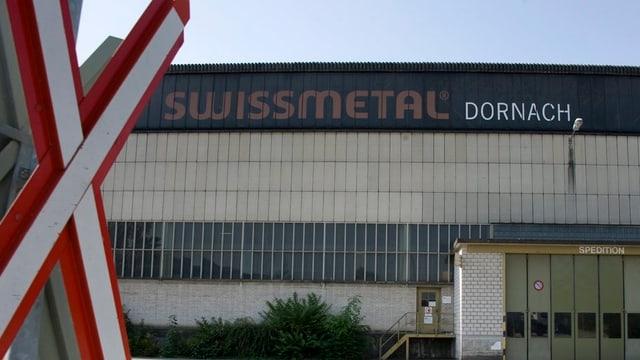 Ein Gebäude von Swissmetal in Dornach im Hintergrund.Im Vorergrund ein Barrierensignal der Bahn.
