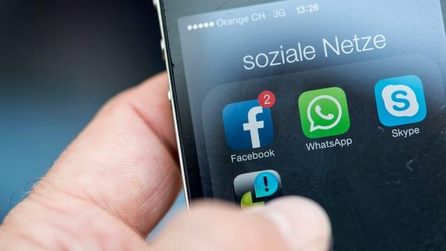 Ein Mann will auf seinem iPhone die Apps Facebook und Whatsapp benutzen.