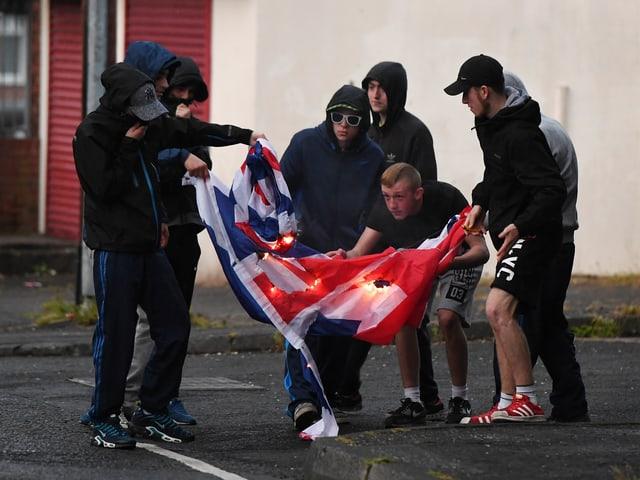 Schwarz gekleidete Jugendliche verbrennen auf der Strasse eine Union Jack-Flagge.