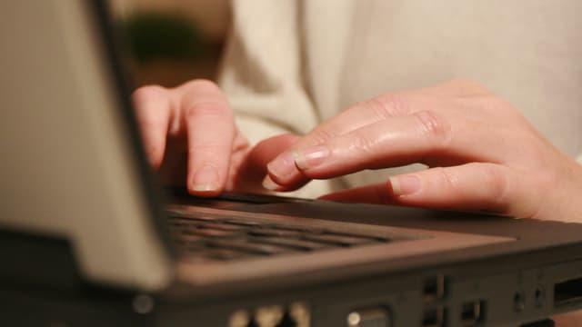 Hände am tippen an einem Laptop