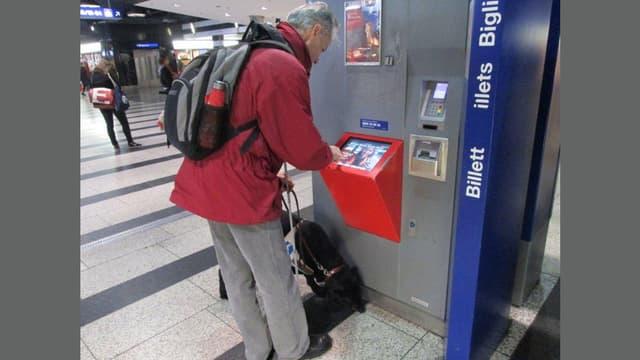 Ein blinder Mann versucht am Billettautomaten zurecht zu kommen.